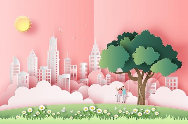 Styl sztuki papieru z cute para siedzi na huśtawce pod drzewem w dużym mieście. Premium Wektorów