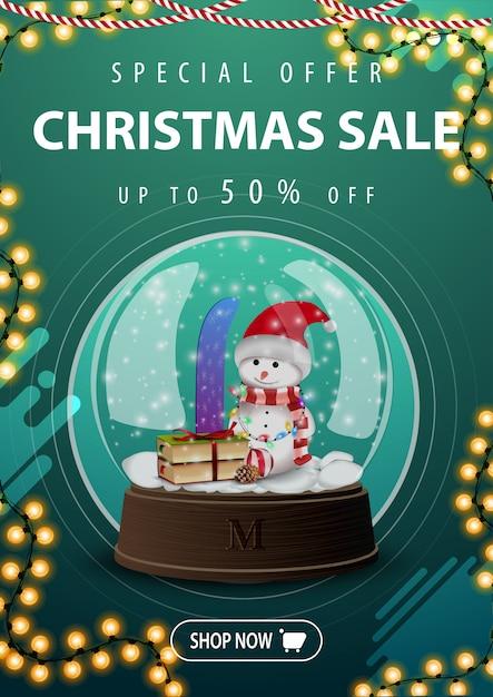Świąteczna Wyprzedaż, Do 50% Zniżki, Pionowy Zielony Sztandar Rabatowy Z Girlandą I śnieżną Kulą Z Bałwanem Premium Wektorów