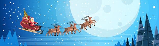 Święty Mikołaj Latający W Sankach Z Reniferami Nocne Niebo Nad Księżycem Na Boże Narodzenie | Premium Wektor