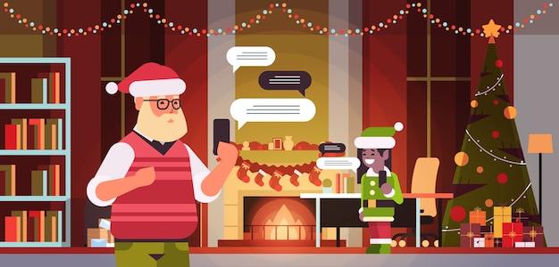 Święty Mikołaj Z Elfem Pomocnikiem Rozmawiającym Za Pomocą Aplikacji Mobilnej Na Smartfonie Sieć Społecznościowa Czat Bańka Koncepcja Komunikacji Nowoczesny Salon Wnętrze Portret Poziomy Ilustracji Wektorowych Premium Wektorów