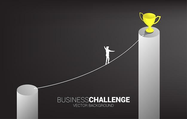 Sylwetka biznesmen chodzenie po linie spacer sposób na złote trofeum na wyższym wykresie słupkowym Premium Wektorów