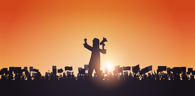 Sylwetka Mężczyzna Z Megafonem Nad Tłumem Protestujący Trzymający Protest Plakaty Mężczyzna Kobiety Głosowanie Plakaty Wolność Demonstracja Polityczna Portret Premium Wektorów