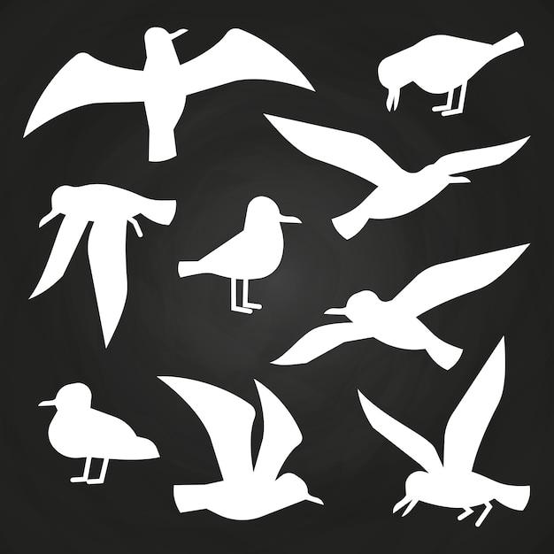 Sylwetki białych ptaków na tablicy - latające mewy sylwetki Premium Wektorów