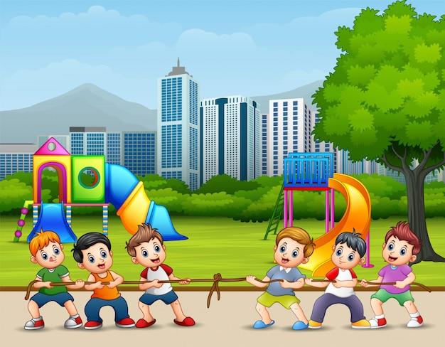 Szczęśliwe dzieci bawiące się w przeciąganie liny w parku miejskim Premium Wektorów