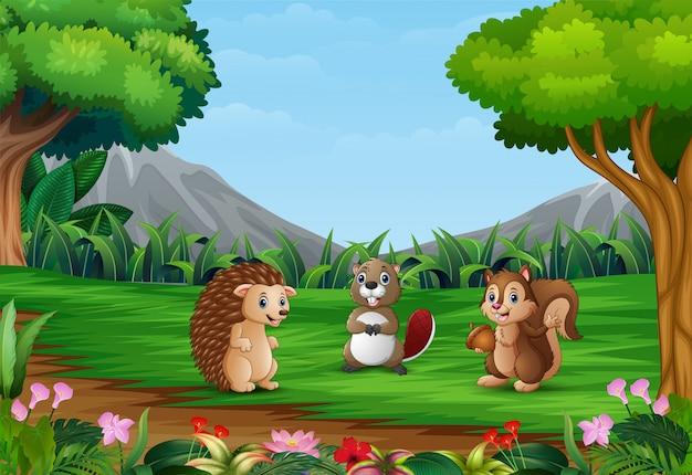 Szczęśliwe małe zwierzęta bawią się w pięknym krajobrazie Premium Wektorów