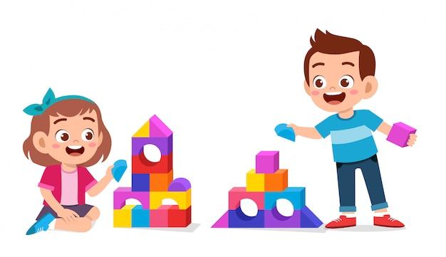 Szczęśliwe Słodkie Dzieci Grają Razem W Blok Z Cegły Premium Wektorów