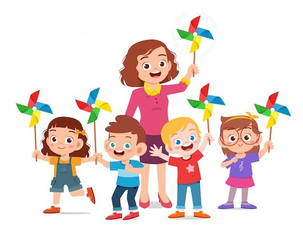 Szczęśliwi śliczni dzieciaki i nauczyciela mienia zabawka Premium Wektorów