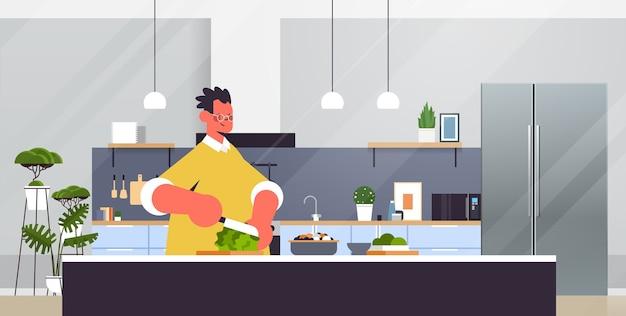 Szczęśliwy Człowiek Cięcia Sałaty Przygotowanie Sałatki Ze świeżych Warzyw Zdrowe Odżywianie Gotowanie W Domu Koncepcja Nowoczesnej Kuchni Wnętrza Poziomy Portret Premium Wektorów