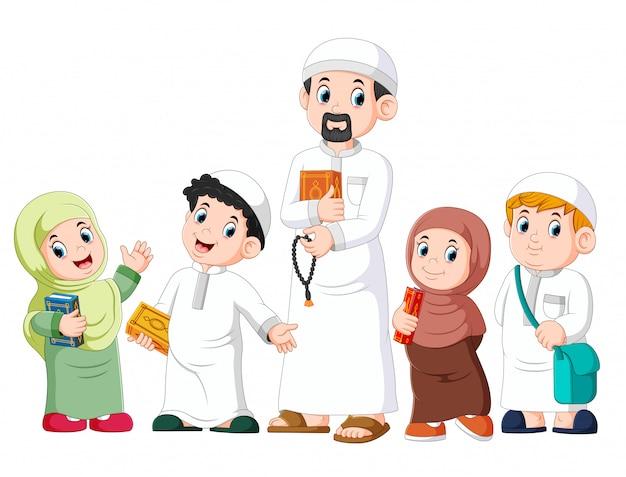 Szczęśliwy muzułmański dzieciak pokazuje z trzymać świętego koran Premium Wektorów