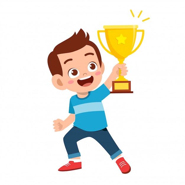Szczęśliwy śliczny dzieciak chłopiec wygrywa gemowego złotego trofeum Premium Wektorów