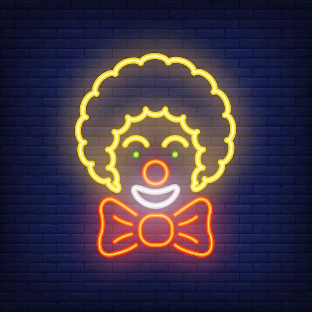 Uśmiechający Się Neon Ikona Klauna. Cyrkowy Artysta Z Dużym łękiem Na Ciemnym ściana Z Cegieł Tle. Darmowych Wektorów
