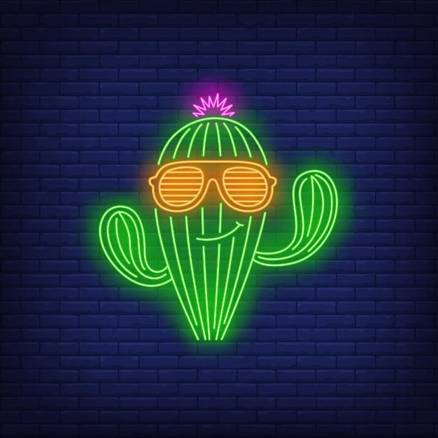Uśmiechnięty kaktusowy charakter jest ubranym okulary przeciwsłoneczni neonowego znaka Darmowych Wektorów