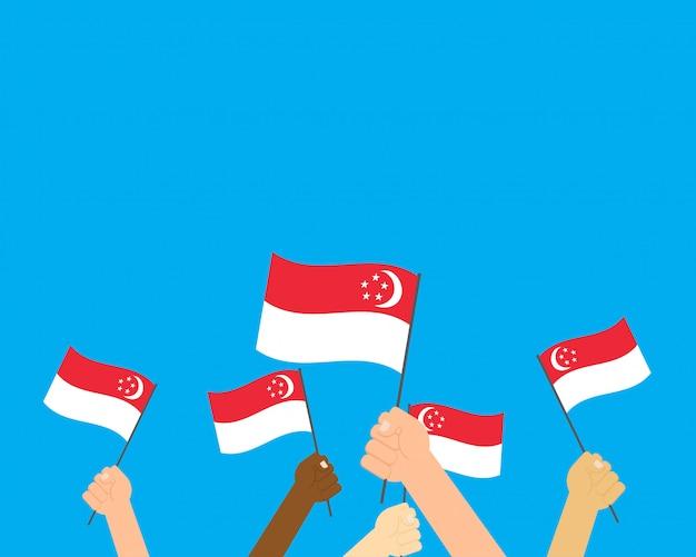 Wektorowe ilustracyjne ręki trzyma singapur flaga Premium Wektorów