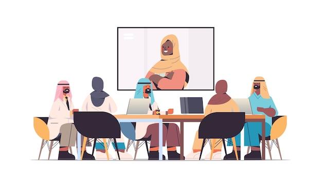 Zespół Arabskich Lekarzy Odbywających Wideokonferencję Z Kobietą Czarnoskórą Muzułmańską Lekarzem Arabskimi Lekarzami Omawiającymi Przy Okrągłym Stole Medycyna Pojęcie Opieki Zdrowotnej Poziome Pełnej Długości Ilustracje Wektorowe Premium Wektorów
