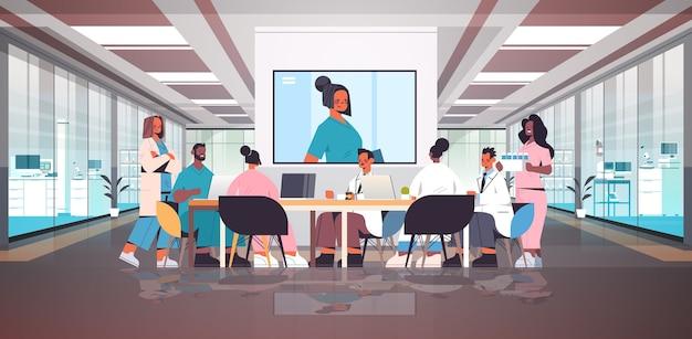 Zespół Lekarzy Posiadających Wideokonferencję Wyścigu Mix Lekarzy Omawiających Przy Okrągłym Stole Medycyna Pojęcie Opieki Zdrowotnej Wnętrze Szpitala Poziome Pełnej Długości Ilustracji Wektorowych Premium Wektorów