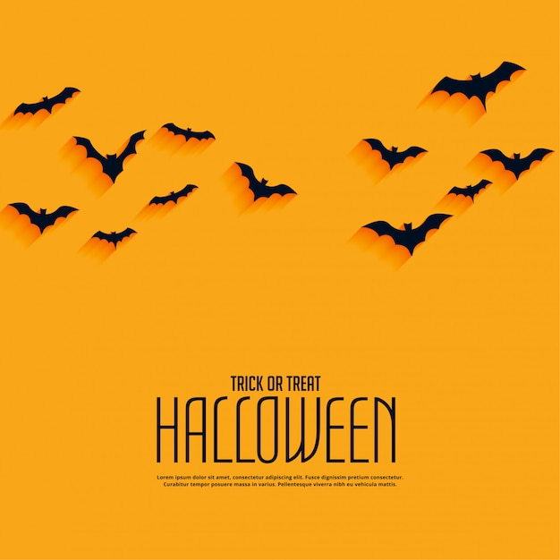 Żółty szczęśliwy halloween tło z latającymi nietoperzami Darmowych Wektorów