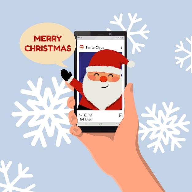 Życzenia Wesołych świąt Z Mediów Społecznościowych. śliczny Mikołaj Uśmiecha Się. Ręka Trzymająca Smartfon. Płaski Wektor Kreskówka. Premium Wektorów