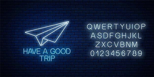 Życzymy Dobrej Podróży świecącym Neonowym Sztandarem Z Papierowym Znakiem Samolotu I Alfabetem Na Ciemnym Murem Premium Wektorów