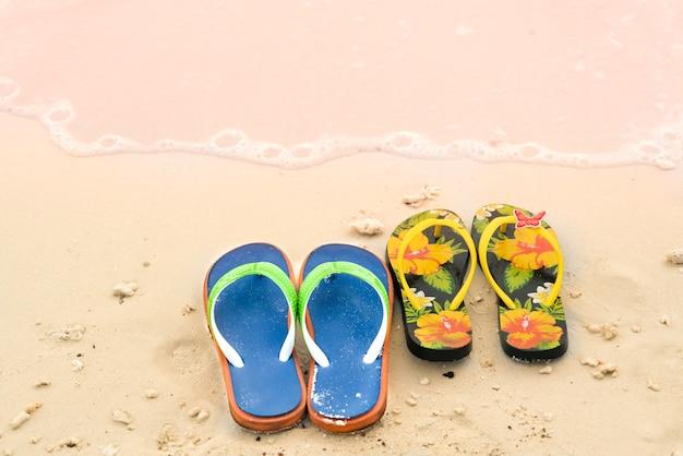 2 Kapcie Na Białej, Piaszczystej Plaży, Czas Podróży I Wakacji Premium Zdjęcia