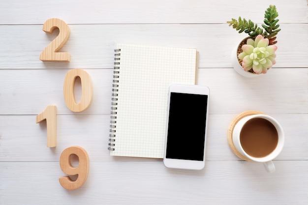 2019 Drewnianych Listów, Pusty Notatnik Papier, Inteligentny Telefon Z Pustego Ekranu Na Biały Drewno Backg Premium Zdjęcia