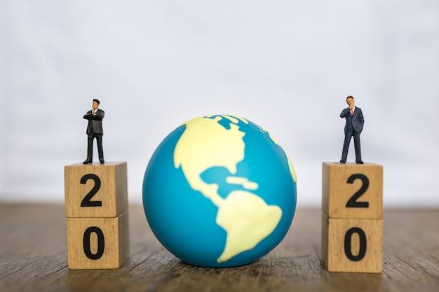2020 Nowy Rok, Koncepcja Globalna I Biznesowa. Zamyka W Górę Dwa Biznesmenów Postaci Miniaturowych Ludzi Stoi Na Górze Sterty Drewniany Liczba Blok I Mini świat Zabawkarska Piłka Z Kopii Przestrzenią Premium Zdjęcia