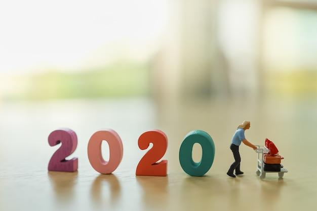2020 Nowy Rok Koncepcja Planowania Podróży. Człowiek Miniaturowa Postać Osób Z Wózkiem Lotniskowym (wózek Bagażowy). Premium Zdjęcia
