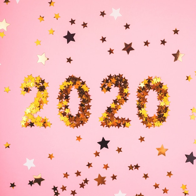 2020 Nowy Rok Symbol Złotych Konfetti Na Różowym Tle. Premium Zdjęcia