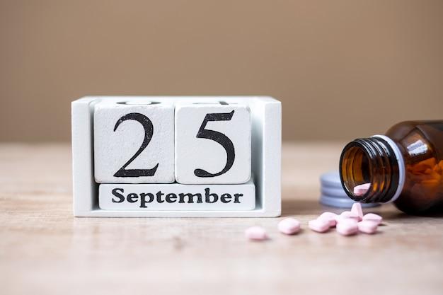 25 września kalendarz drewniany i lek, koncepcja światowego dnia farmaceuty Premium Zdjęcia