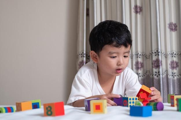 3-letni Mały Azjatycki Chłopiec Gra W Domu W łóżku Na Kwadratowej Układance Premium Zdjęcia