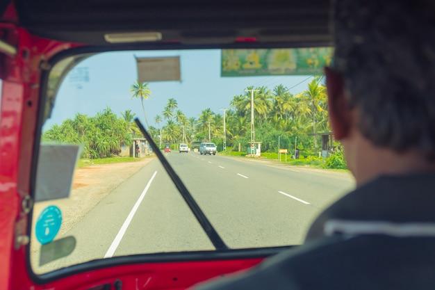 4 marca 2018 r. hikkaduwa, sri lanka. kierowca tuk-tuk w kokpicie Premium Zdjęcia