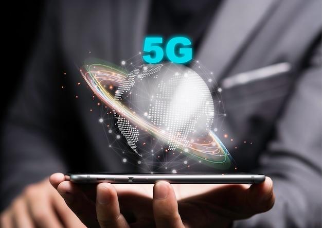 5g I Internet Rzeczy Lub Koncepcja Iot, Biznesmen Posiadający Smartfon Z 5g Na świecie Premium Zdjęcia