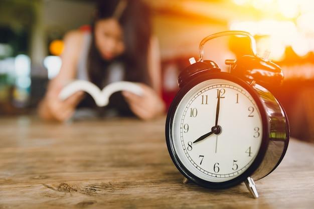 8 godzina retro dzwon zegar z ludźmi czytać tło książki. czytanie każdego dnia koncepcji. Premium Zdjęcia