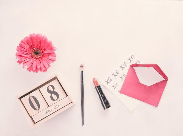 8 marca napis na drewniane klocki z kwiatów i szminki na stole Darmowe Zdjęcia