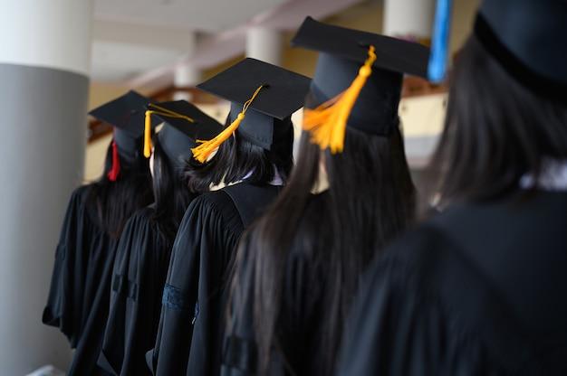 Absolwenci studenccy nosili czarny kapelusz, czarny kapelusz na ceremonii ukończenia studiów na uniwersytecie. Premium Zdjęcia