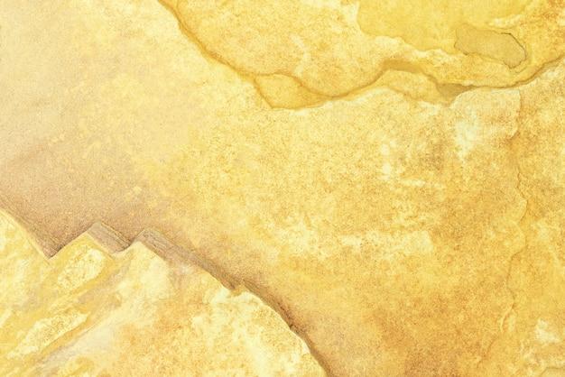 Abstrakcjonistyczny tło od starej żółtej betonowej tekstury ściany z grunge i pękał. Premium Zdjęcia