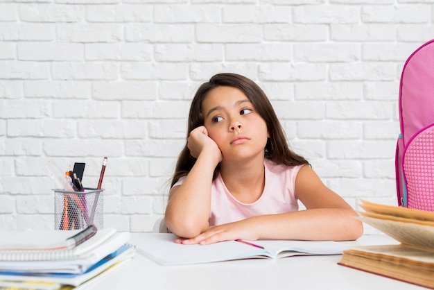 Adorable hispanic znudzona dziewczyna będzie odrabiania lekcji Darmowe Zdjęcia