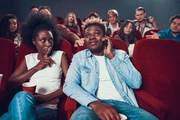 African American Człowiek Rozmawia Przez Telefon Podczas Pokazu Filmowego. Premium Zdjęcia