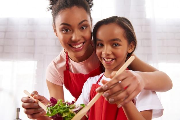 African american matka i córka wymieszać sałatkę Premium Zdjęcia