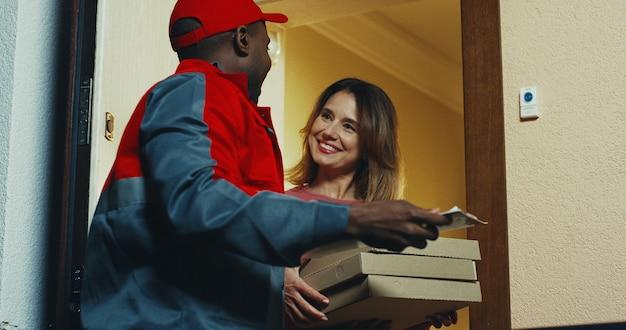 African American Młody Człowiek W Mundurze I Czapce Dostarczający Pizzę Do Rasy Białej. Wewnątrz. Premium Zdjęcia