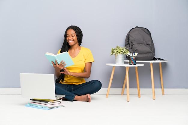 African american nastolatka student dziewczyna z długimi plecionymi włosami siedzi na podłodze i czytając książkę Premium Zdjęcia