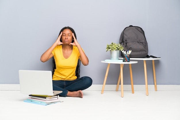 African american nastolatka student dziewczyna z długimi plecionymi włosami siedzi na podłodze niezadowolony i sfrustrowany Premium Zdjęcia
