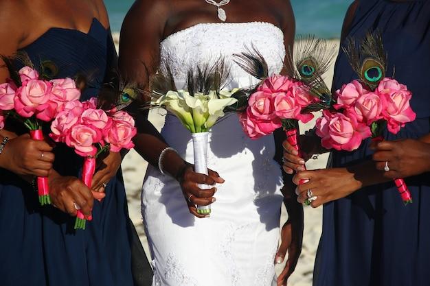 African American Oblubienicy Na Białej Sukni Wraz Z Druhny Gospodarstwa Kolorowe Bukiety Kwiatów W Dniu ślubu Na Zewnątrz. Premium Zdjęcia