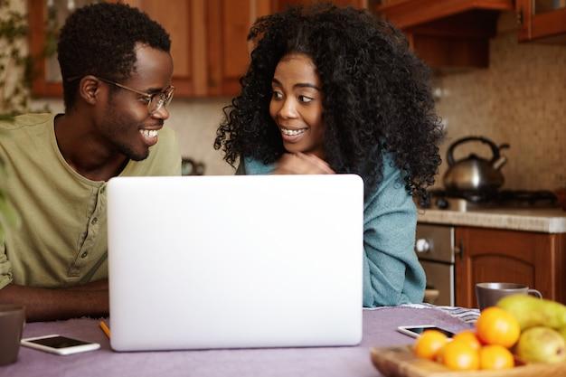 African-american Para Razem Przy Użyciu Komputera Przenośnego W Domu. Szczęśliwa Kobieta Uśmiecha Się I Patrzy Na Męża Z Podekscytowaniem, Kupując Bilety Lotnicze Online, Planując Spędzić Wakacje Nad Morzem Darmowe Zdjęcia