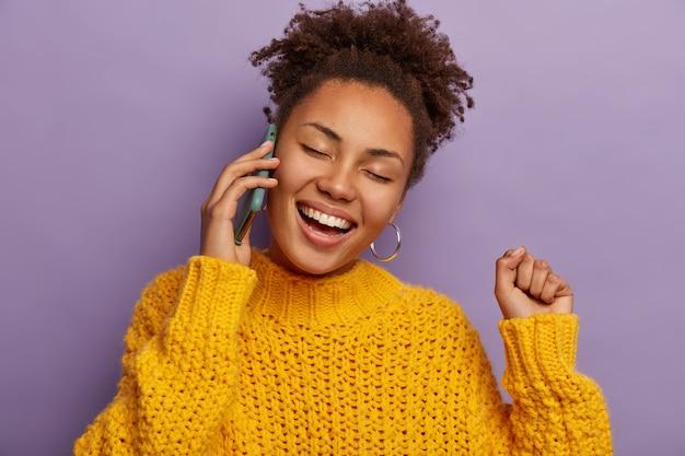 Afro Prowadzi Rozmowę Telefoniczną, Prowadzi Zabawną Zabawną Rozmowę, Podnosi Zaciśniętą Pięść, Szeroko Się Uśmiecha Na Fioletowym Tle Darmowe Zdjęcia