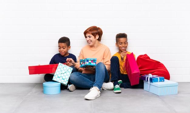 Afroamerykanie dzieci z matką wśród wielu prezentów na święta bożego narodzenia Premium Zdjęcia