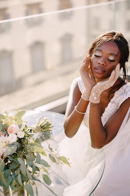 Afroamerykanka Siedzi Przy Stole, Dotyka Jej Twarzy Rękawiczkami W Dłoniach, Bukiet Leży Na Stole Premium Zdjęcia