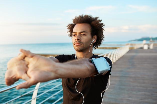 Afroamerykański Biegacz O Pięknym Atletycznym Ciele I Krzaczastych Włosach Rozciągających Mięśnie, Unoszący Ramiona Podczas Rozgrzewki Przed Poranną Sesją Treningową. Darmowe Zdjęcia