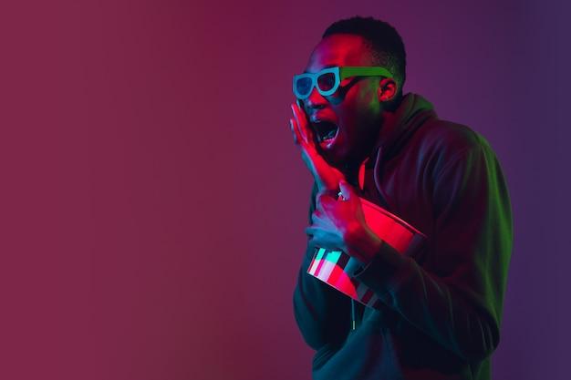 Afroamerykański Mężczyzna Portret Odizolowywający Na Gradient ścianie W Neonowym świetle Darmowe Zdjęcia