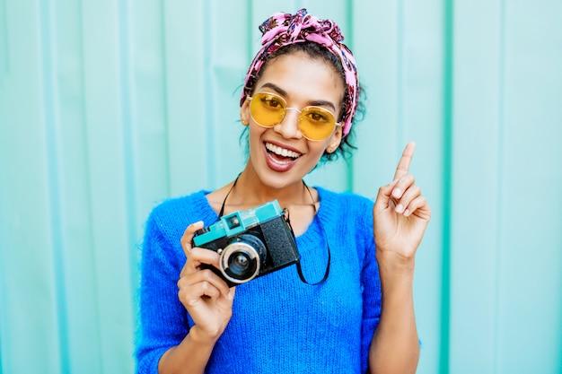 Afrykańska Kobieta W Jasnym Wełnianym Swetrze I Kolorowej Opasce Na Włosach Trzyma Kamerę Filmową. Darmowe Zdjęcia