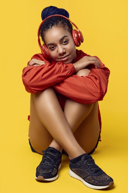 Afrykańska Nastoletnia Dziewczyna Z Dreadlocks W Czerwonym Wiatrówka Słucha Muzykę Premium Zdjęcia